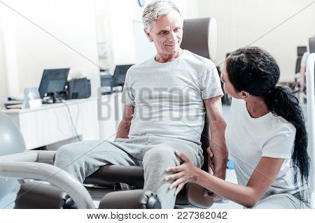 Making Success. Cheerful Old Crippled Grey-haired Man Smiling And Exercising On A Training Device Wh