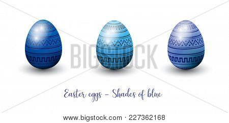 Three decorative three-dimentional glossy easter eggs in shades of blue.