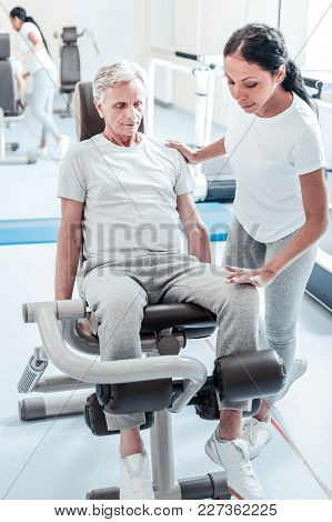 Training Hard. Concentrated Old Crippled Grey-haired Man Exercising On A Training Device While A Ser