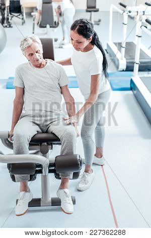 Exercising Hard. Concentrated Old Grey-haired Man Exercising On A Training Device While A Serious Yo