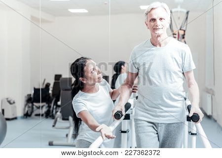 Improving Heath. Vigorous Old Wrinkled Grey-haired Man Smiling And Exercising On A Training Device W