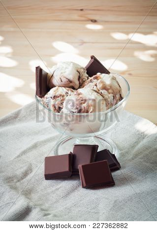Vanilla Ice Cream Scoops With Chocolate In Bowl On Wooden Background