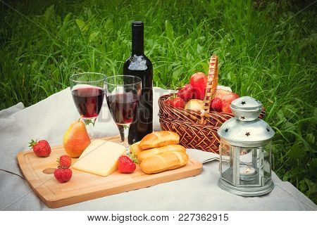Outdoor Picnic Setting With Glasses And Bottle Of Red Wine, Lantern, Cheese  And Fruits