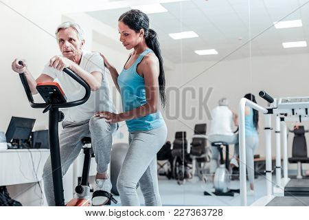 Training Legs. Concentrated Aged Grey-haired Man Exercising On A Training Device And Training His Le