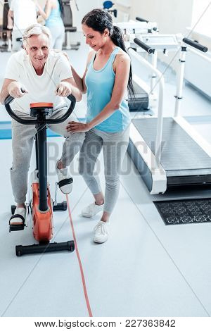 Doing Sport. Happy Smiling Aged Grey-haired Man Exercising On A Training Device And Training His Leg