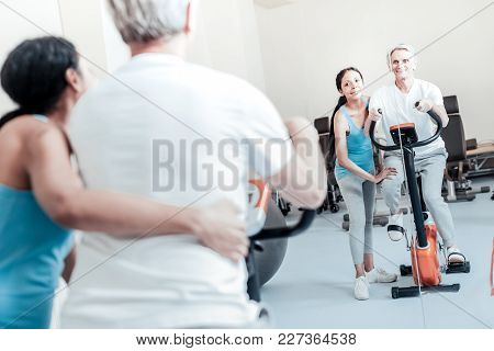 Smile. Exuberant Old Grey-haired Man Exercising On A Training Device And An Alert Young Dark-haired