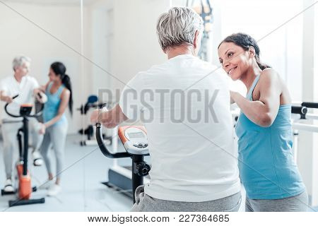Smile To Me. Old Grey-haired Man Dressed In White Shirt Exercising On A Training Device While A Beau
