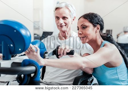 Setting A Device. Cheerful Old Grey-haired Man Exercising On A Training Device And Sitting In A Whee