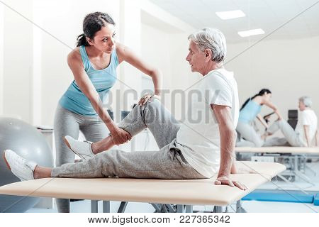 Stretching Legs. Serious Old Grey-haired Man Sitting On Bed While A Concentrated Young Dark-haired A