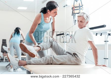 Training Legs. Serious Old Grey-haired Man Sitting On Bed While A Concentrated Young Dark-haired Afr