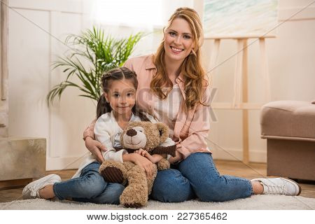 Happy Mother And Little Daughter With Teddy Bear Sitting Together And Smiling At Camera At Home