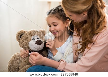 Beautiful Happy Mother And Daughter Playing With Teddy Bear At Home