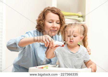 Mother teaching daughter to brush teeth in bathroom