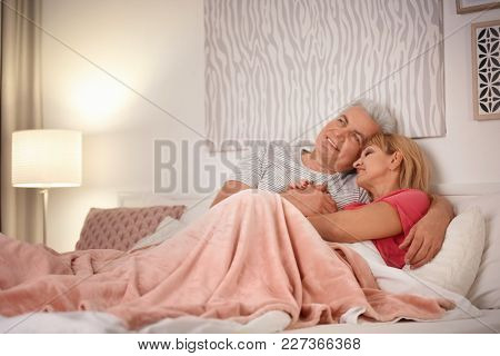 Mature couple hugging in bed. Romantic evening
