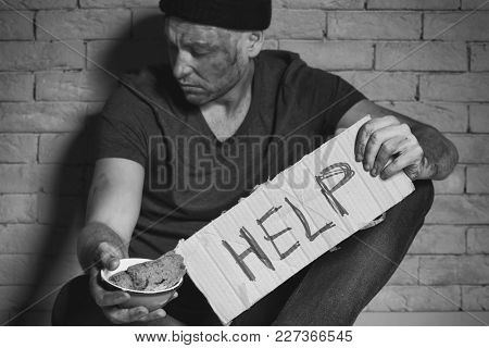 Homeless poor man holding carton board with word HELP and bowl for donations while sitting near brick wall
