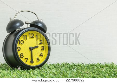 Closeup Beautiful Alarm Clock Show The Time On Half Past Two O'clock Or 2:30 P.m. On Green Artificia