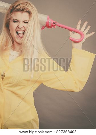 Good Mood During Rainy Day. Happy Blonde Woman Wearing Yellow Raincoat Holding Closed Umbrella