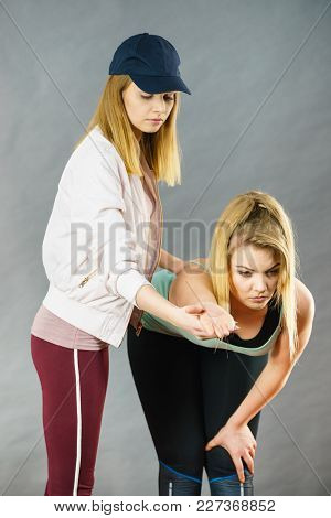 Young Blonde Woman In Sportswear Stretching Body, Working Out With Her Female Trainer. Training At H