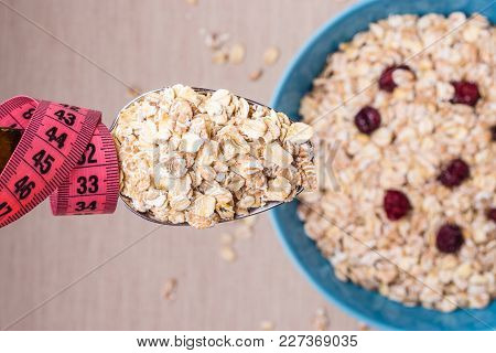 Diet Healthy Food Weight Loss Concept. Oatmeal In Blue Bowl And Pink Measuring Tape Around Spoon On