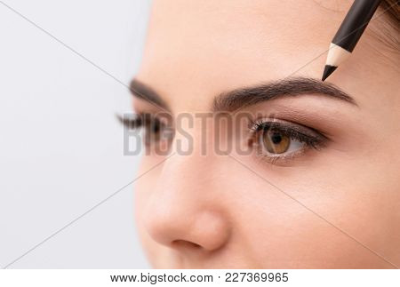 Young woman correcting shape of eyebrows on light background, closeup