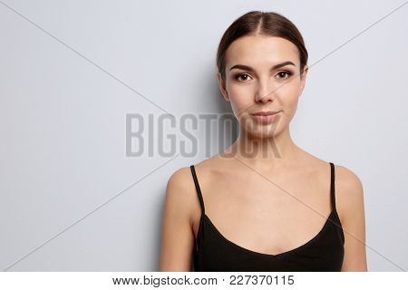 Young woman with beautiful eyebrows on light background