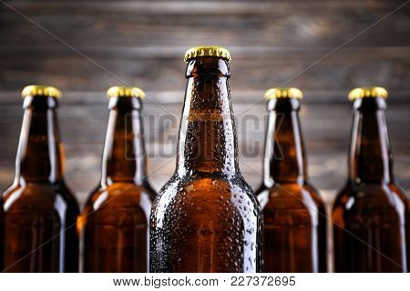 Fresh beer in glass bottles on blurred background, closeup