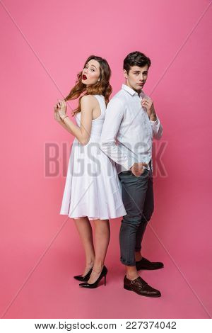 Photo of young serious loving couple isolated over pink background. Looking camera.