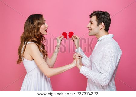 Image of young happy loving couple standing isolated over pink background holding two halves of heart. Looking aside.