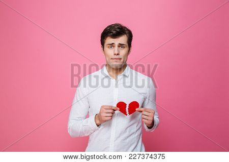 Photo of young sad man standing isolated over pink background holding broken heart. Looking camera.