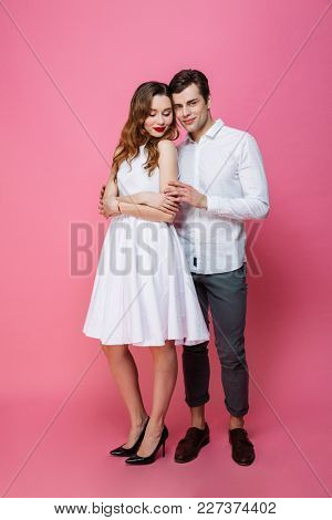 Photo of young happy amazing loving couple isolated over pink background.