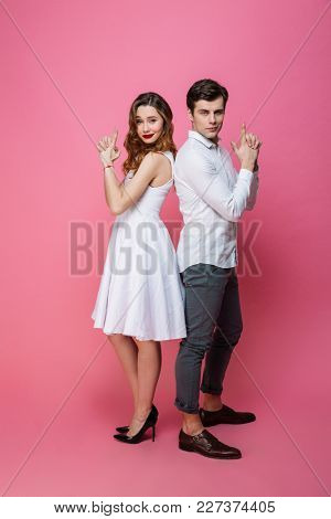 Picture of young amazing loving couple isolated over pink background imagine that they holding guns make gun gesture. Looking camera.