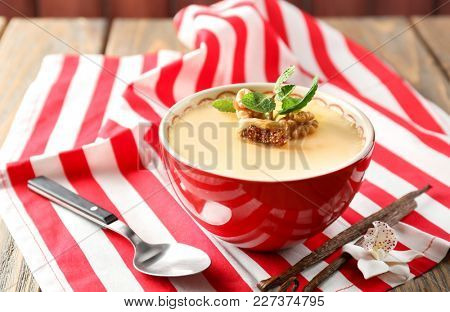 Bowl with tasty vanilla pudding on table