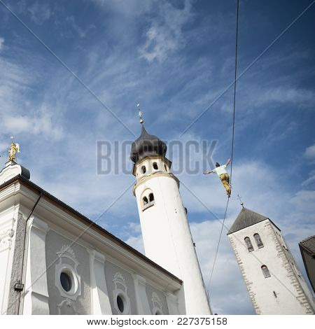 Tightrope Walker, Man Hanging On A Rope Walks In The Sky Between Bell Towers And Churches
