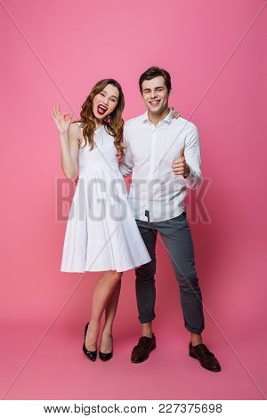 Full length portrait of a cheerful smartly dressed couple showing ok gesture and thumbs up isolated over pink background