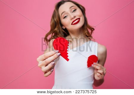 Photo of young cute woman standing isolated over pink background give you half of heart. Looking camera. Focus on heart.