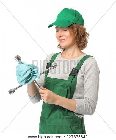 Female auto mechanic wiping lug wrench with rag on white background