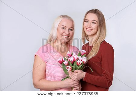 Young daughter and mother with bouquet of flowers on light background