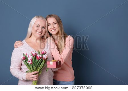 Young daughter with mother holding bouquet of flowers and gift box on color background