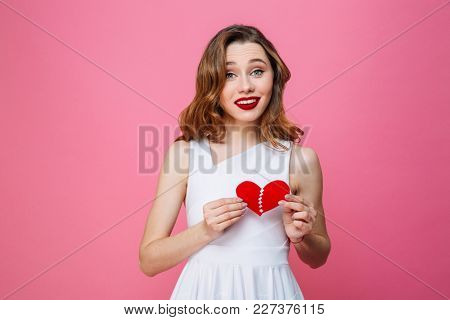 Photo of young cute woman standing isolated over pink background holding two halves of heart. Looking camera.