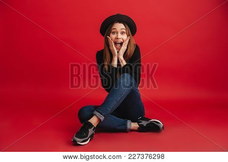 Portrait of an excited stylish girl wearing hat screaming while sitting isolated over red background