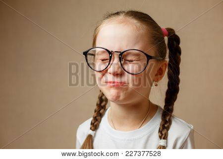 A Little Girl With Glasses And A White T-shirt With Her Eyes Closed