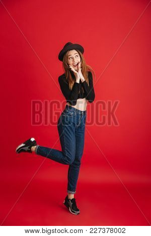 Photo of young excited woman posing isolated over red background. Looking aside.
