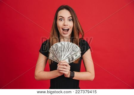 Portrait of an excited girl holding bunch of money banknotes and looking at camera isolated over pink background