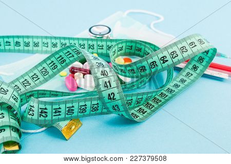 Slimming And Dieting Concept With Centimeter Tape And Pills.