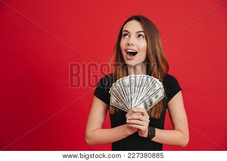 Portrait of an excited girl holding bunch of money banknotes and looking away at copy space isolated over pink background