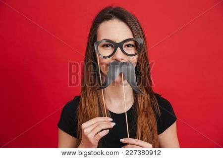 Portrait of a funny girl grimacing with fake eyeglasses and fake moustaches isolated over pink background poster