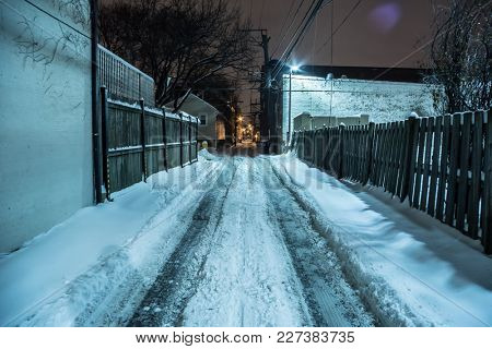 Snow covered dark urban city alley in the winter at night.