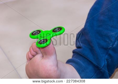 Boy Playing With Fidget Spinner Gadget. The Fidget Spinner Is A Toy, A Small Spit, The Rotating Body