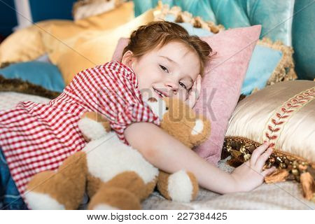 Adorable Kid Lying With Teddy Bear And Smiling At Camera