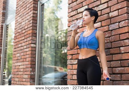 Young Woman Runner Is Having Break, Drinking Water While Jogging In City Center, Copy Space